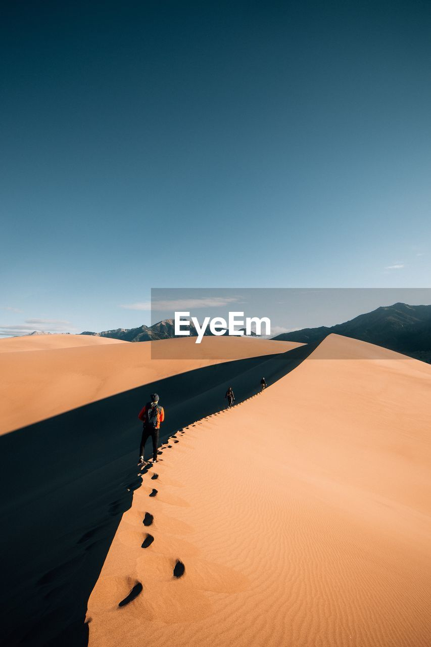 Rear View Of People Walking On Sand Dune At Desert Against Blue Sky