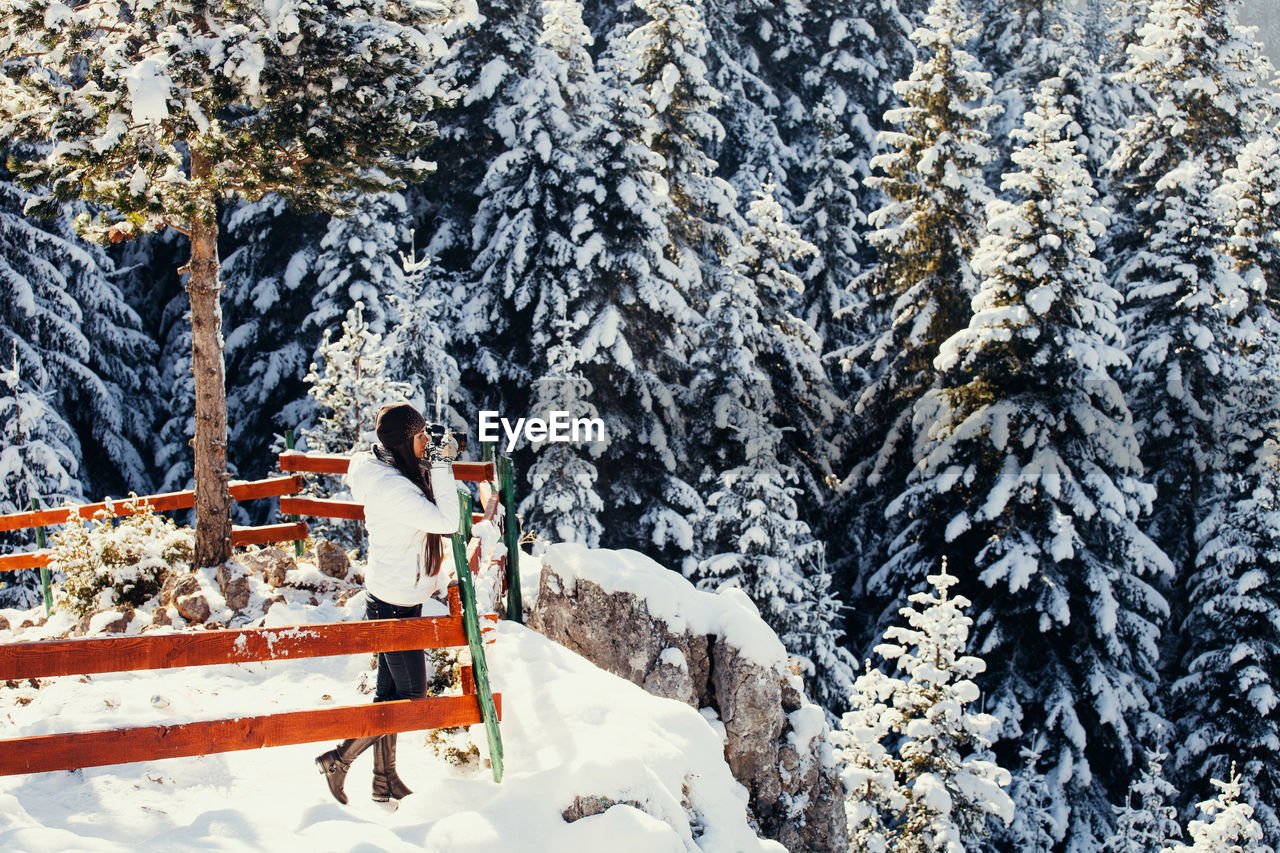 Woman Drinking Tea While Standing On Snow Covered Mountain