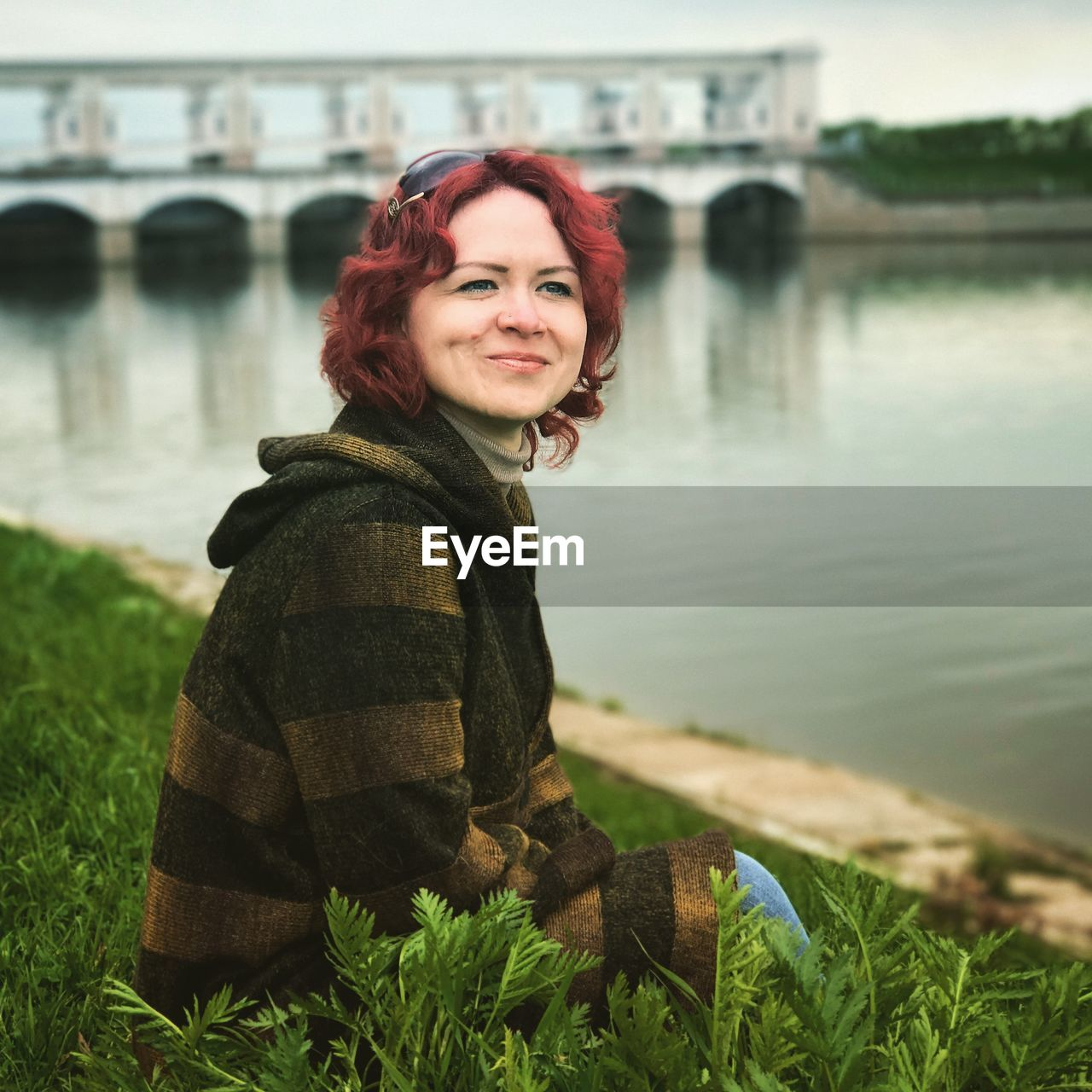 Portrait of smiling young woman against river