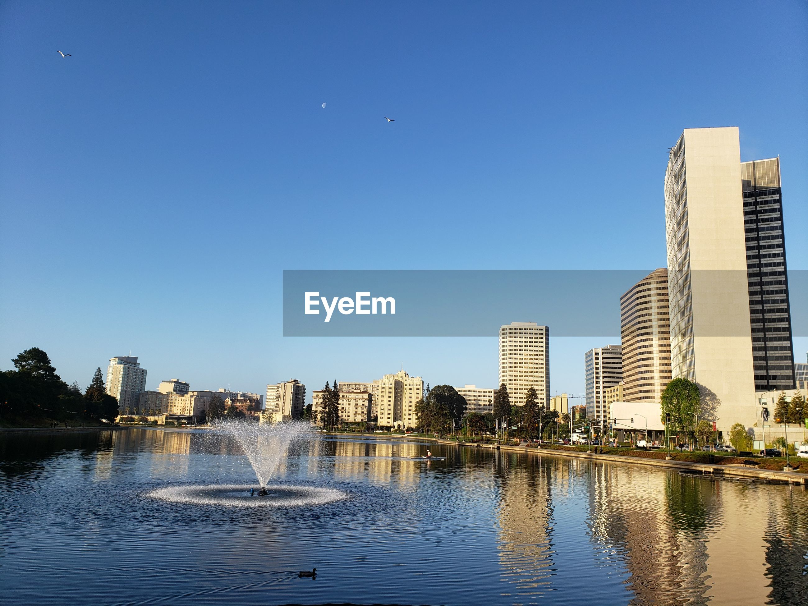 Lake and buildings against clear sky