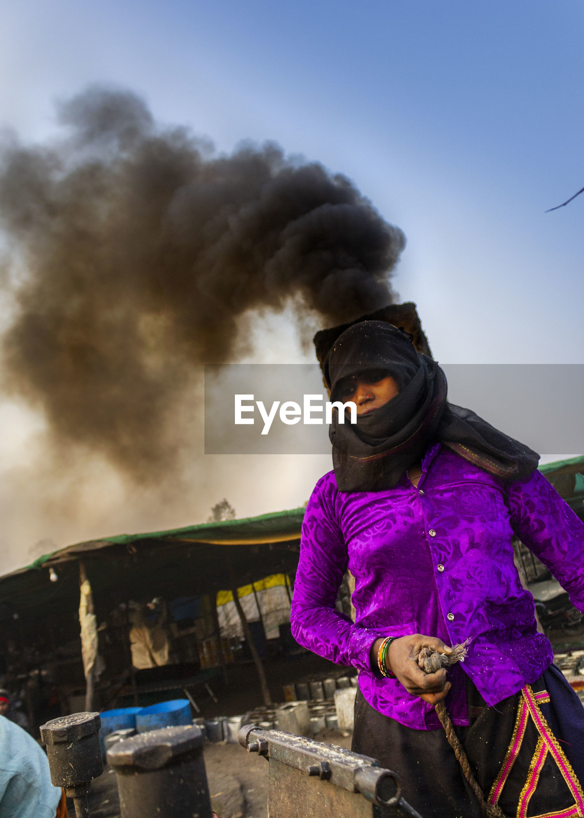 Woman standing at factory emitting smoke against sky