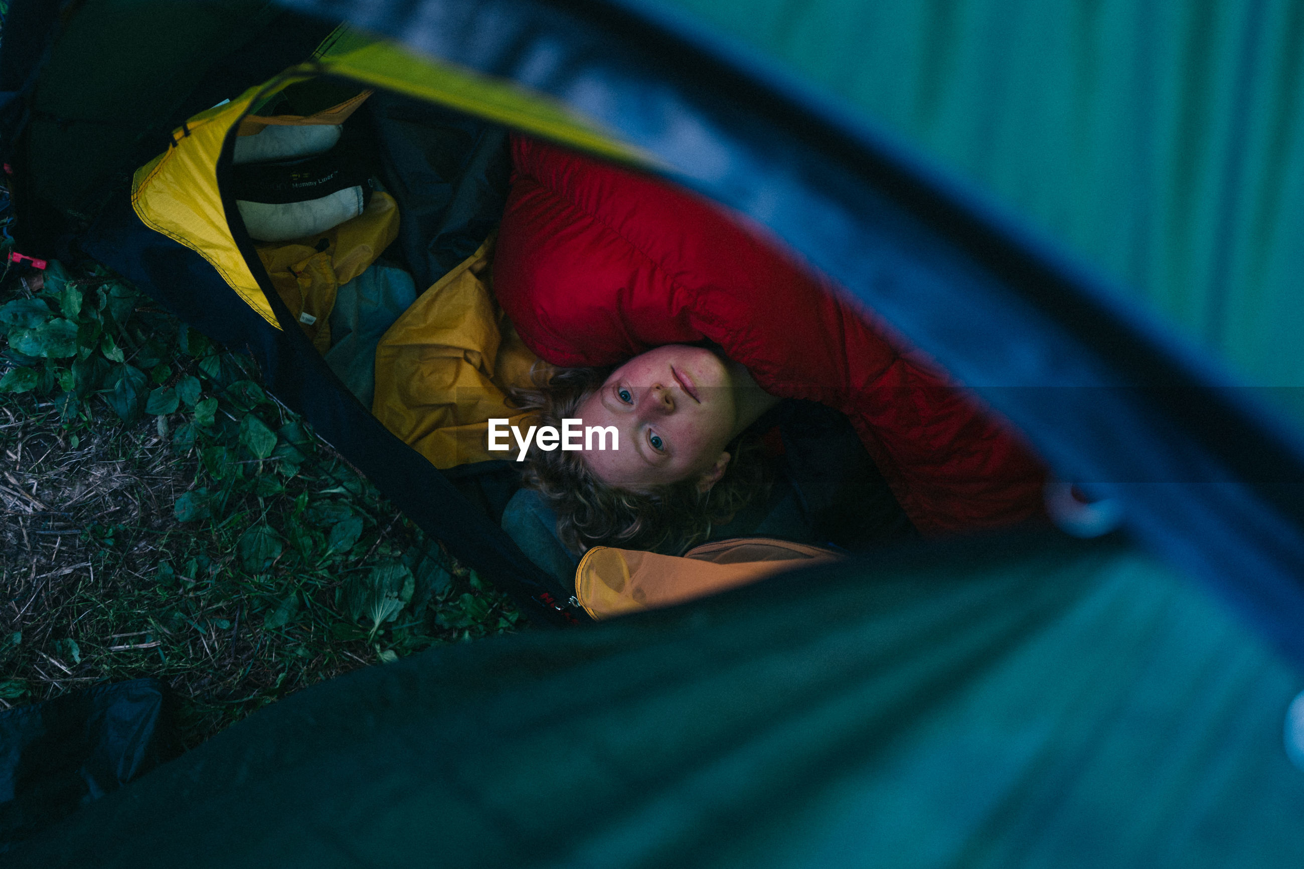 High angle view of woman lying in tent