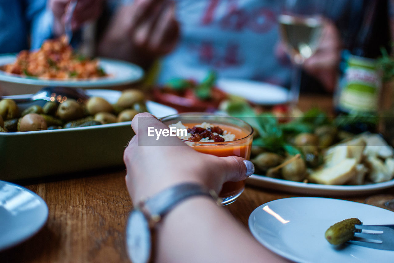 Cropped Image Of Hand Holding Food In Bowl On Table