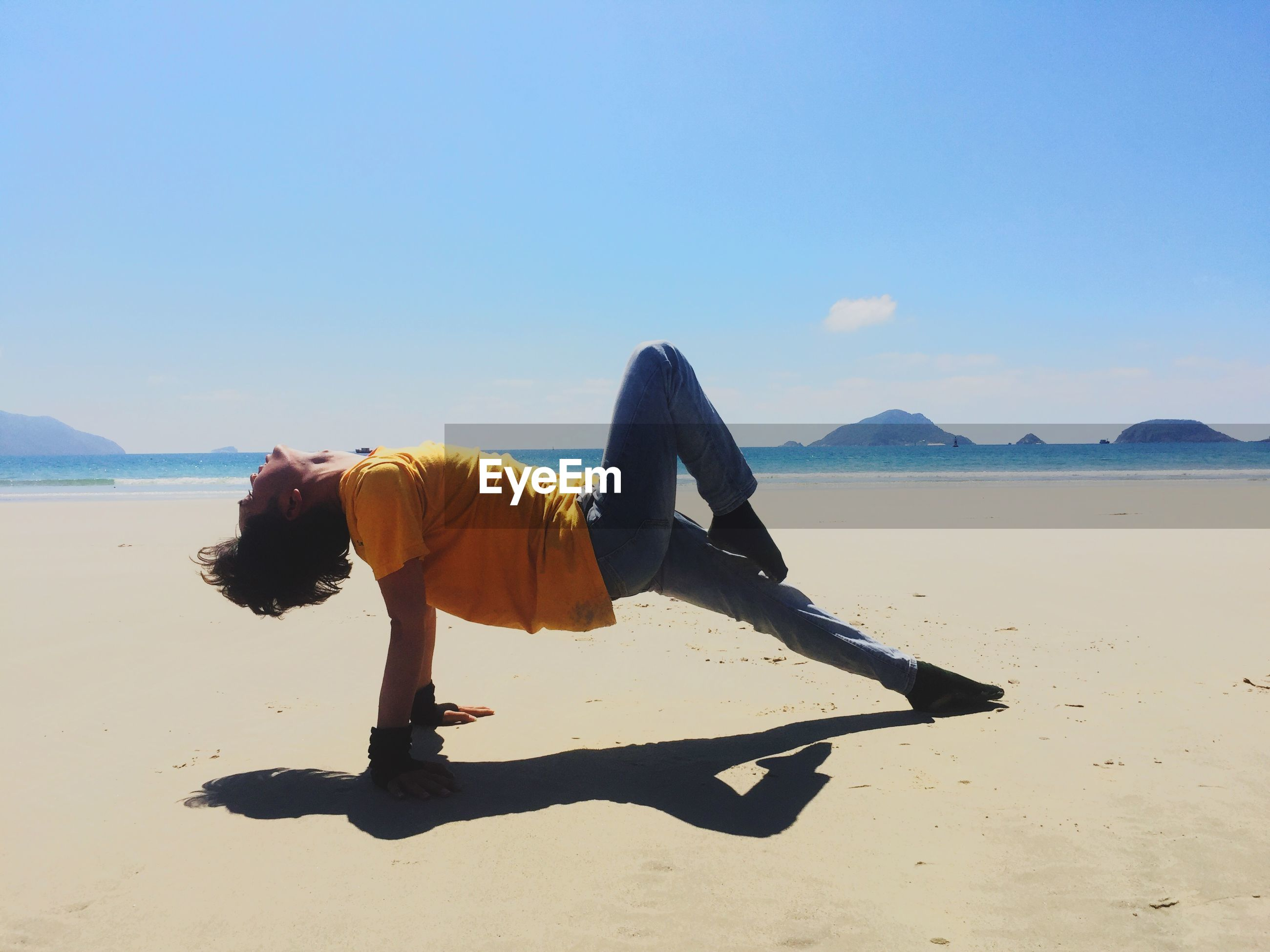 Man bending at beach against sky