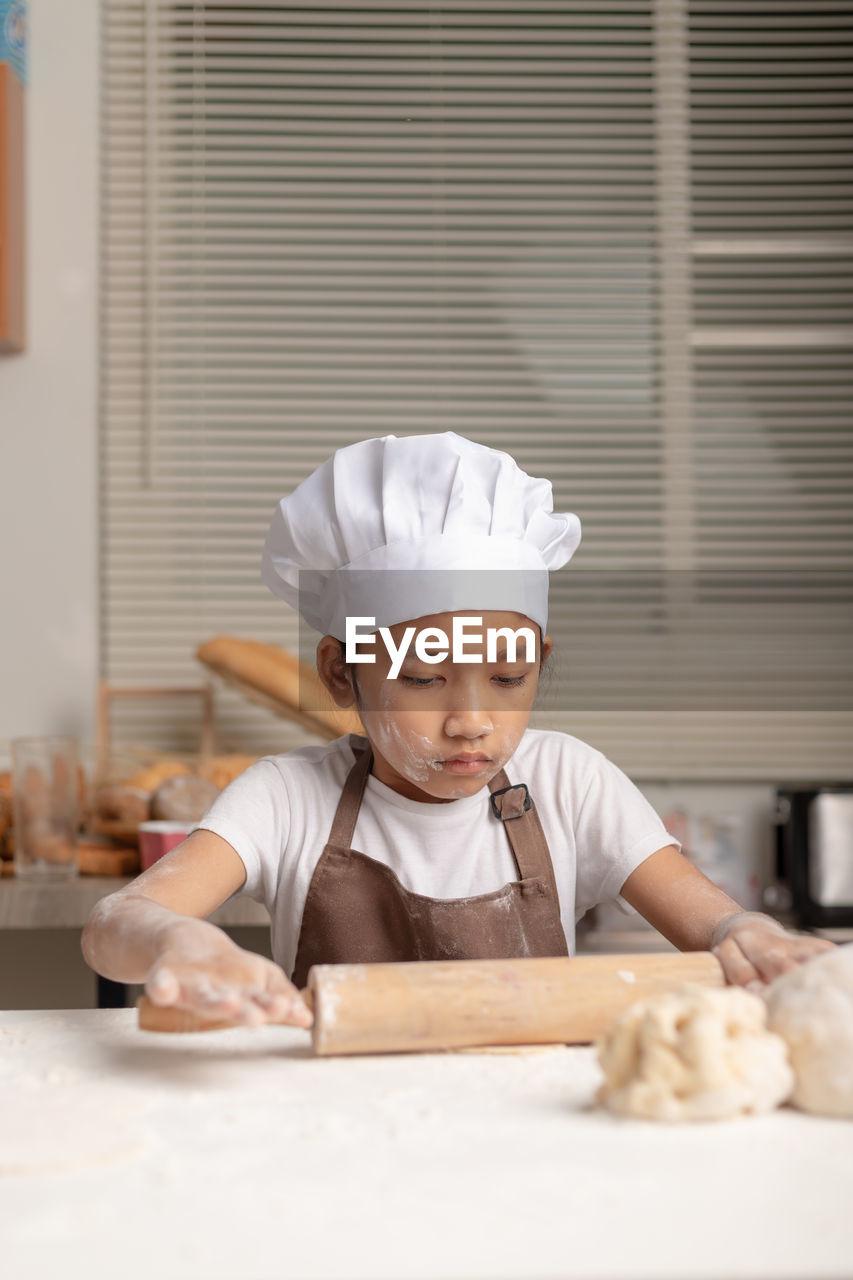Cute girl making cookies at home