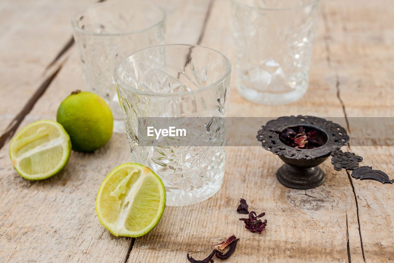 food and drink, fruit, healthy eating, food, glass, citrus fruit, household equipment, slice, freshness, wood - material, lemon, refreshment, drinking glass, no people, wellbeing, drink, table, indoors, still life, focus on foreground