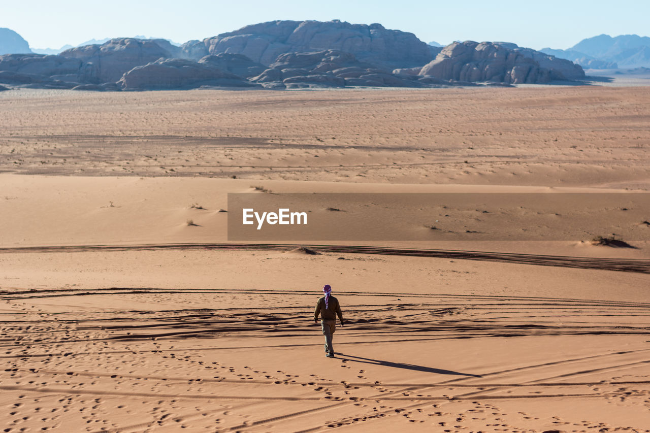 Full length rear view of man walking on desert
