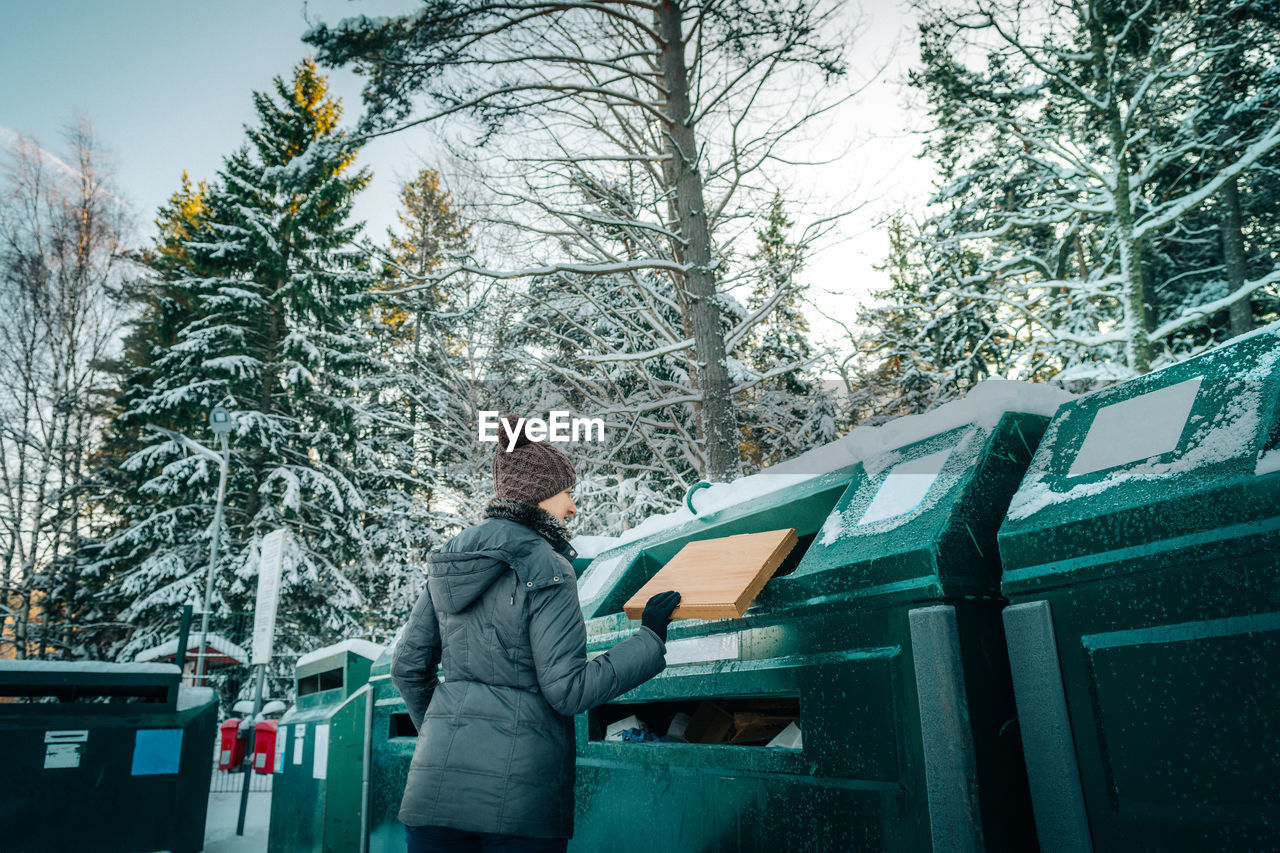 Woman putting cardboard box in garbage can during winter