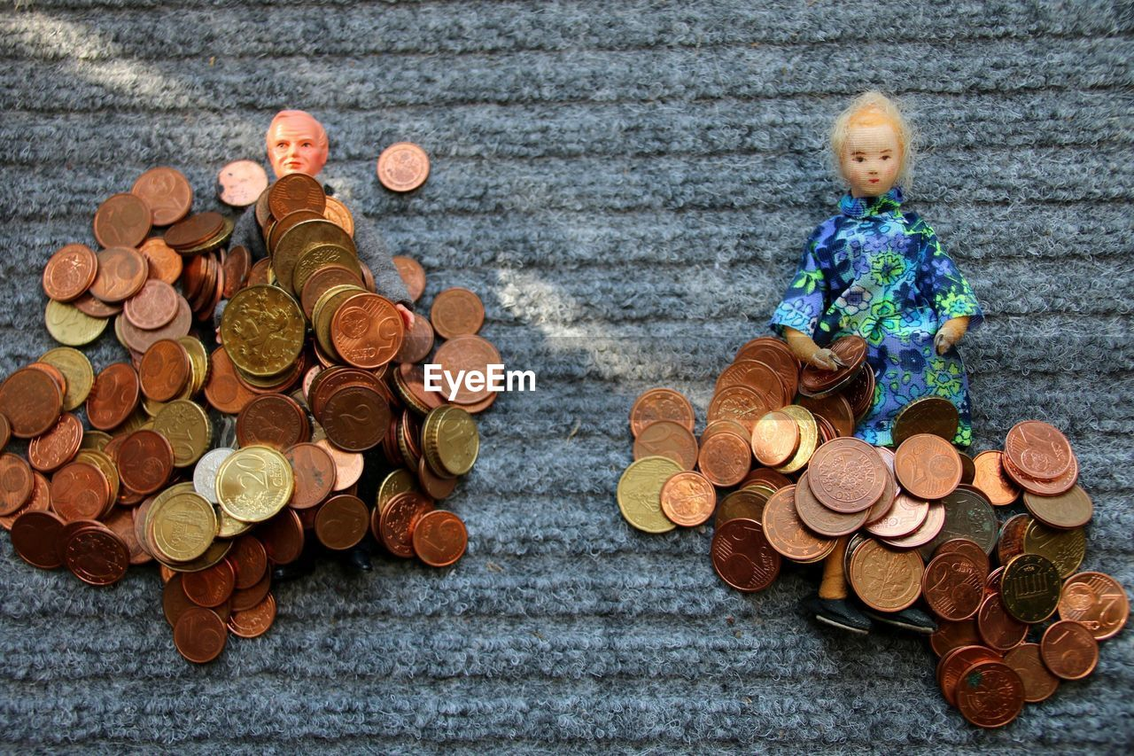 Close-Up Of Coins With Dolls On Table