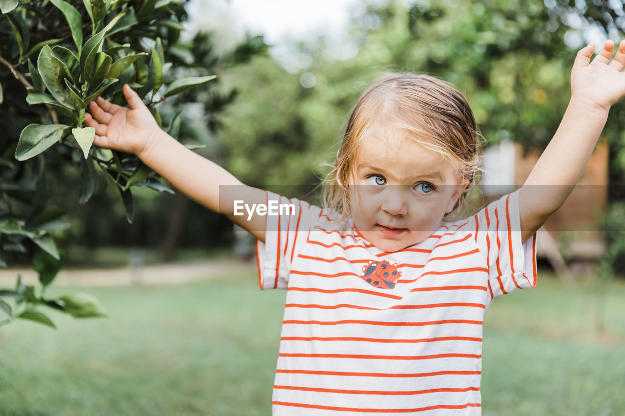 childhood, child, looking at camera, girls, portrait, real people, human arm, one person, front view, arms raised, females, casual clothing, plant, innocence, cute, focus on foreground, striped, lifestyles, outdoors, human limb