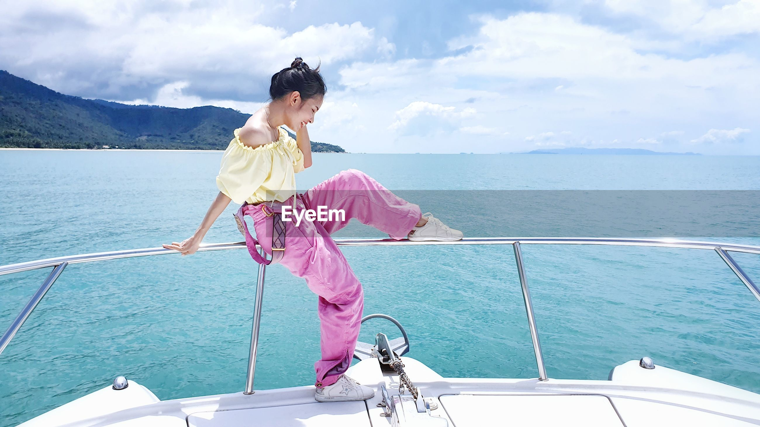 Woman sitting on railing of boat at sea