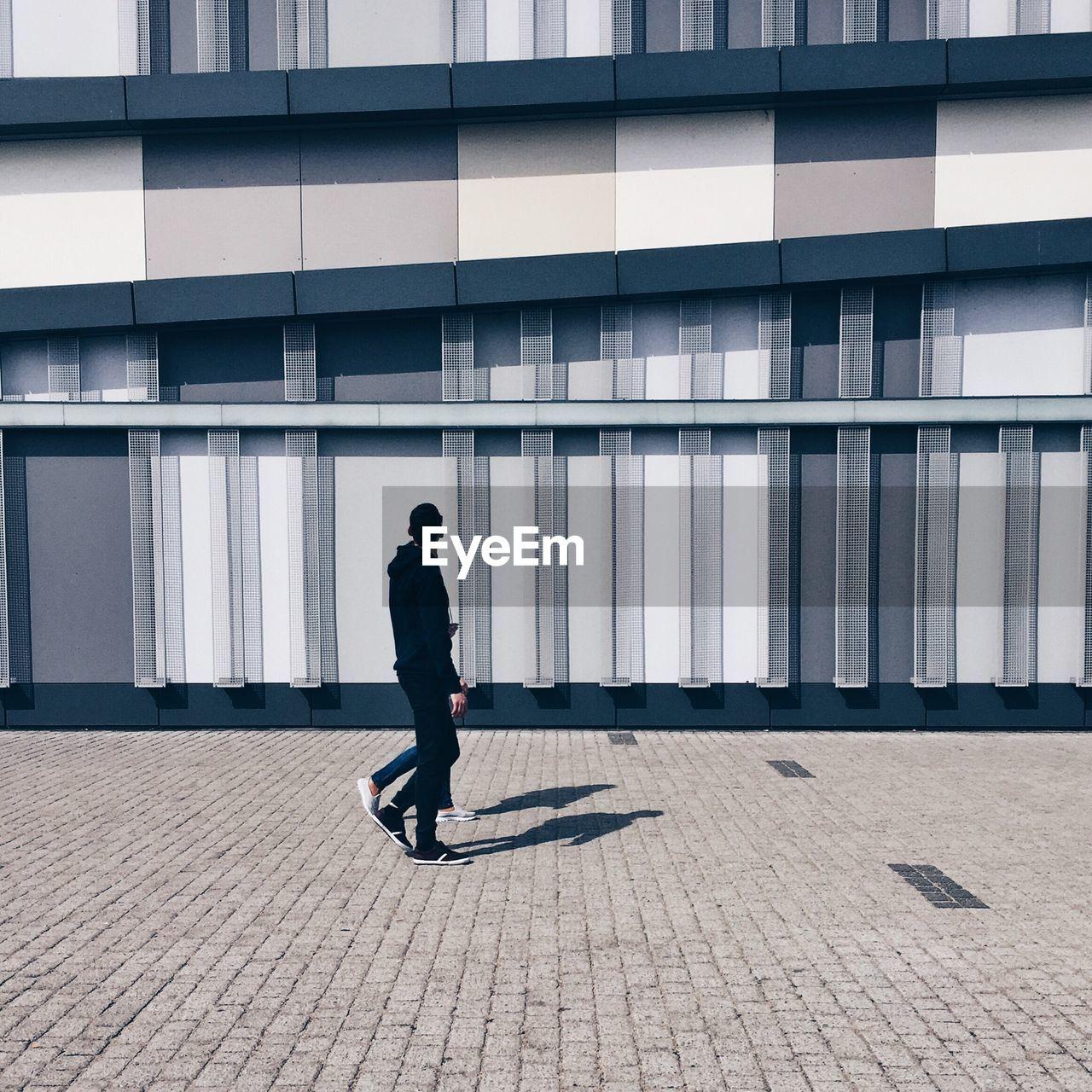 Friends Walking On Footpath Against Building