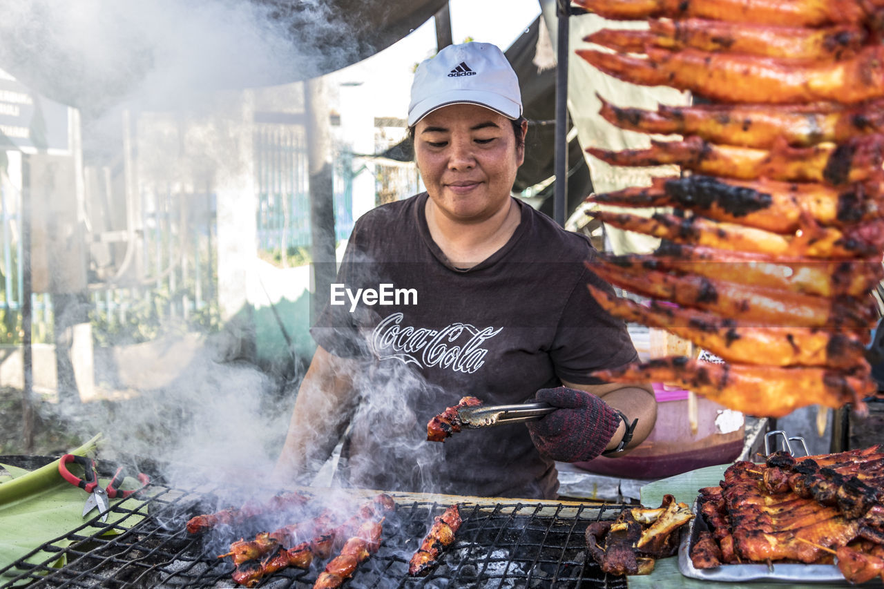 real people, one person, meat, food, front view, food and drink, smoke - physical structure, portrait, mid adult, looking at camera, barbecue, lifestyles, barbecue grill, holding, freshness, leisure activity, emotion, smiling, men, outdoors, preparation, preparing food