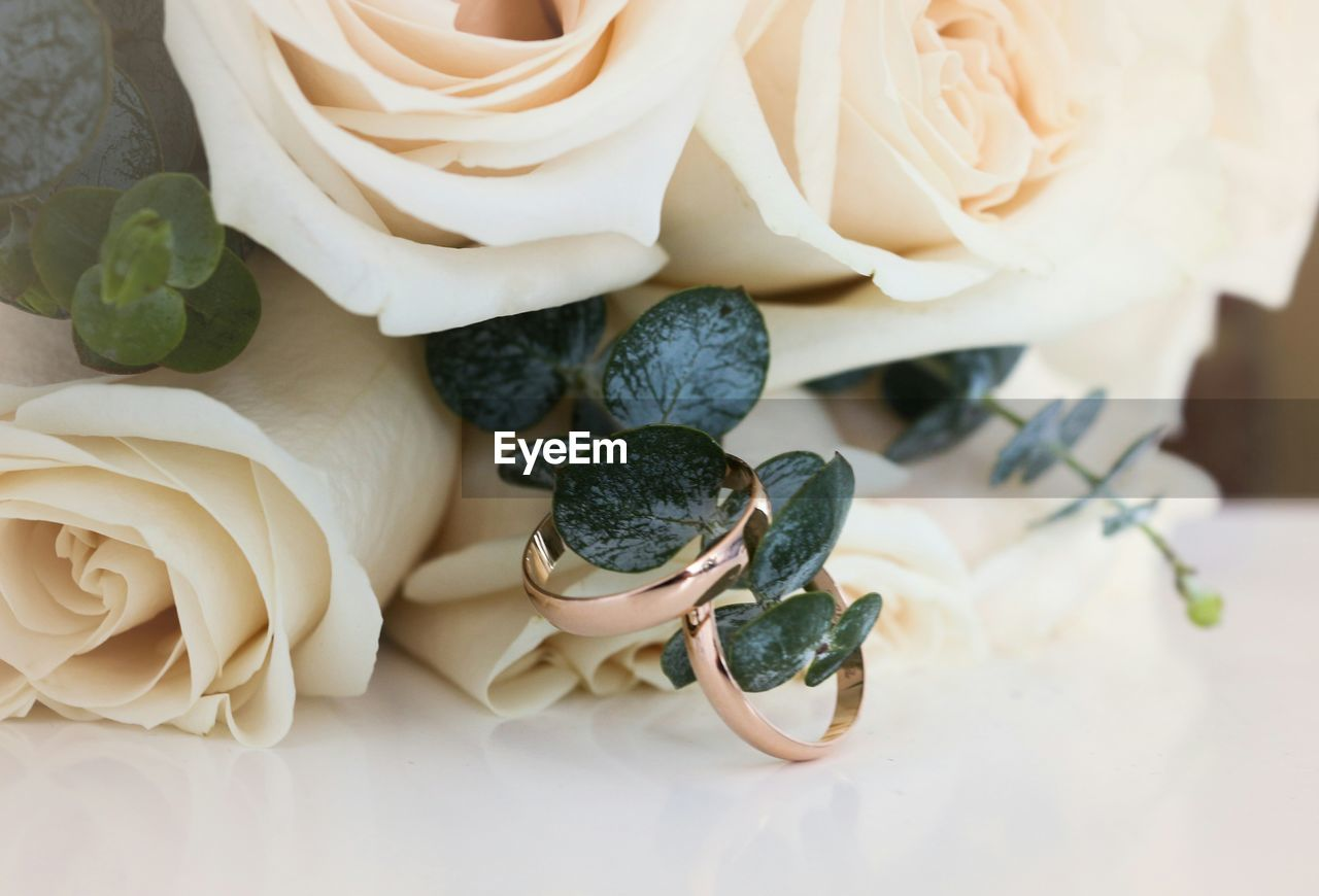 Close-up of wedding rings with bouquet on table