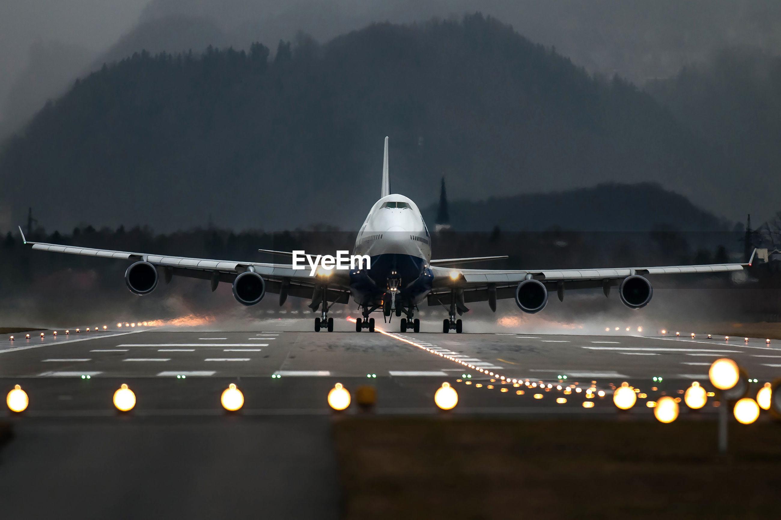 Airplane on illuminated runway against mountain range