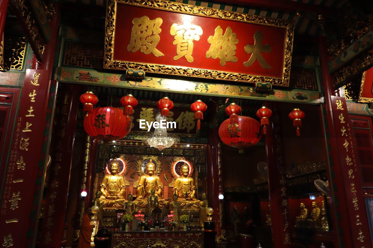 illuminated, lighting equipment, text, architecture, non-western script, built structure, communication, script, red, lantern, building exterior, night, hanging, no people, place of worship, decoration, chinese lantern