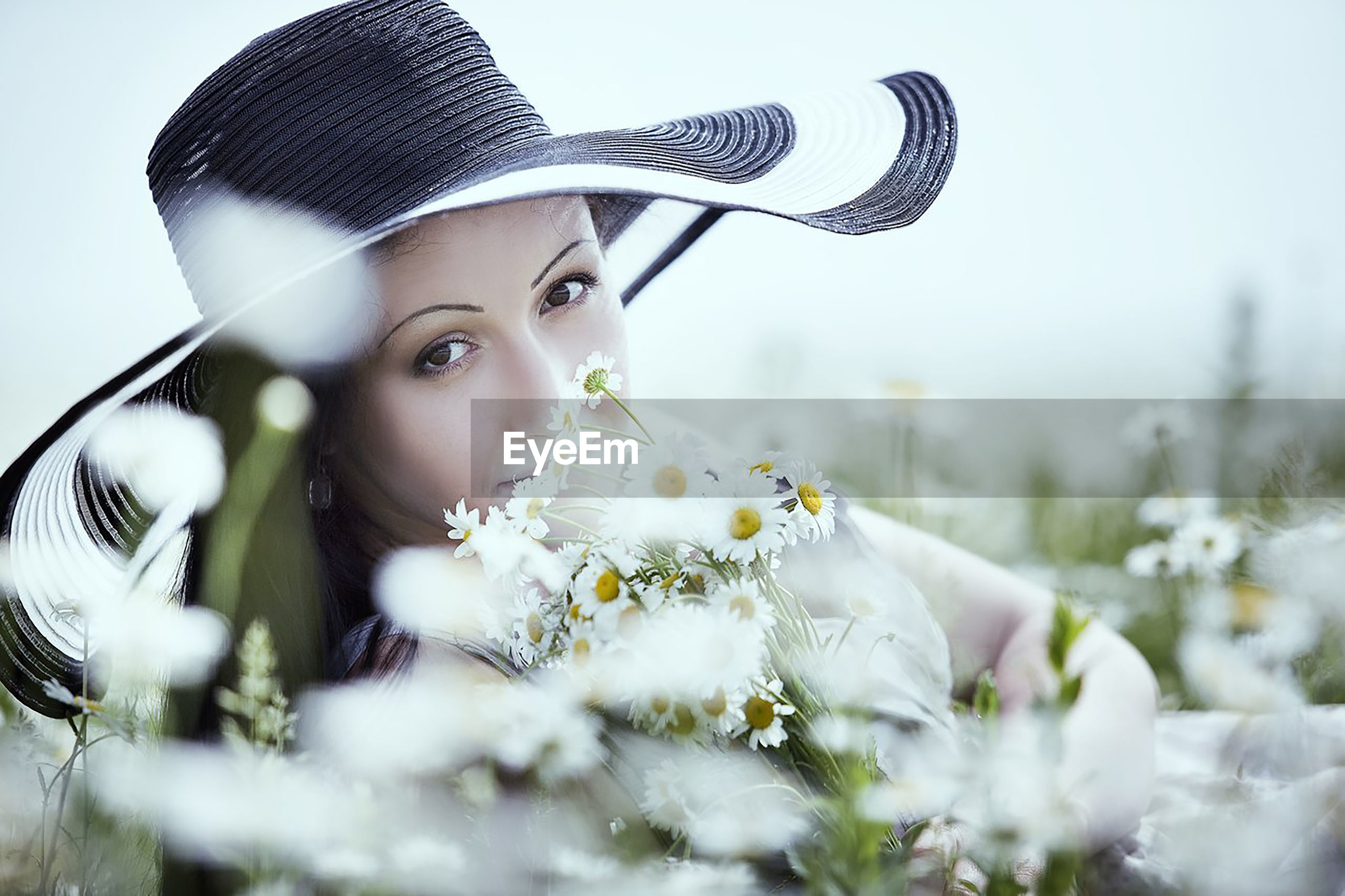 Portrait of woman with flowers on field