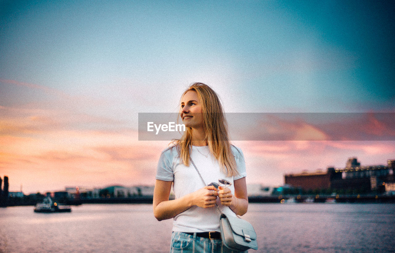sky, sunset, water, one person, standing, young adult, lifestyles, transportation, hair, young women, blond hair, casual clothing, nature, leisure activity, real people, nautical vessel, architecture, cloud - sky, hairstyle, outdoors, beautiful woman