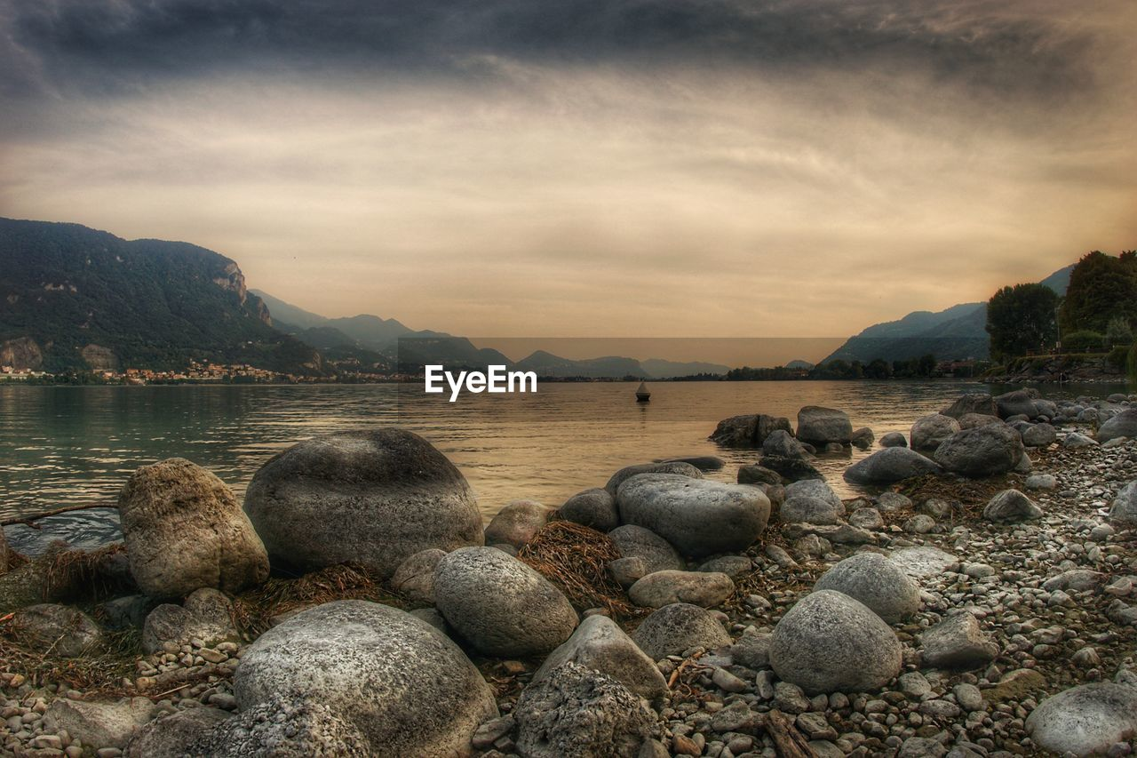 water, sky, rock, mountain, solid, scenics - nature, beauty in nature, cloud - sky, rock - object, tranquility, nature, tranquil scene, lake, no people, beach, mountain range, land, stone, outdoors, pebble