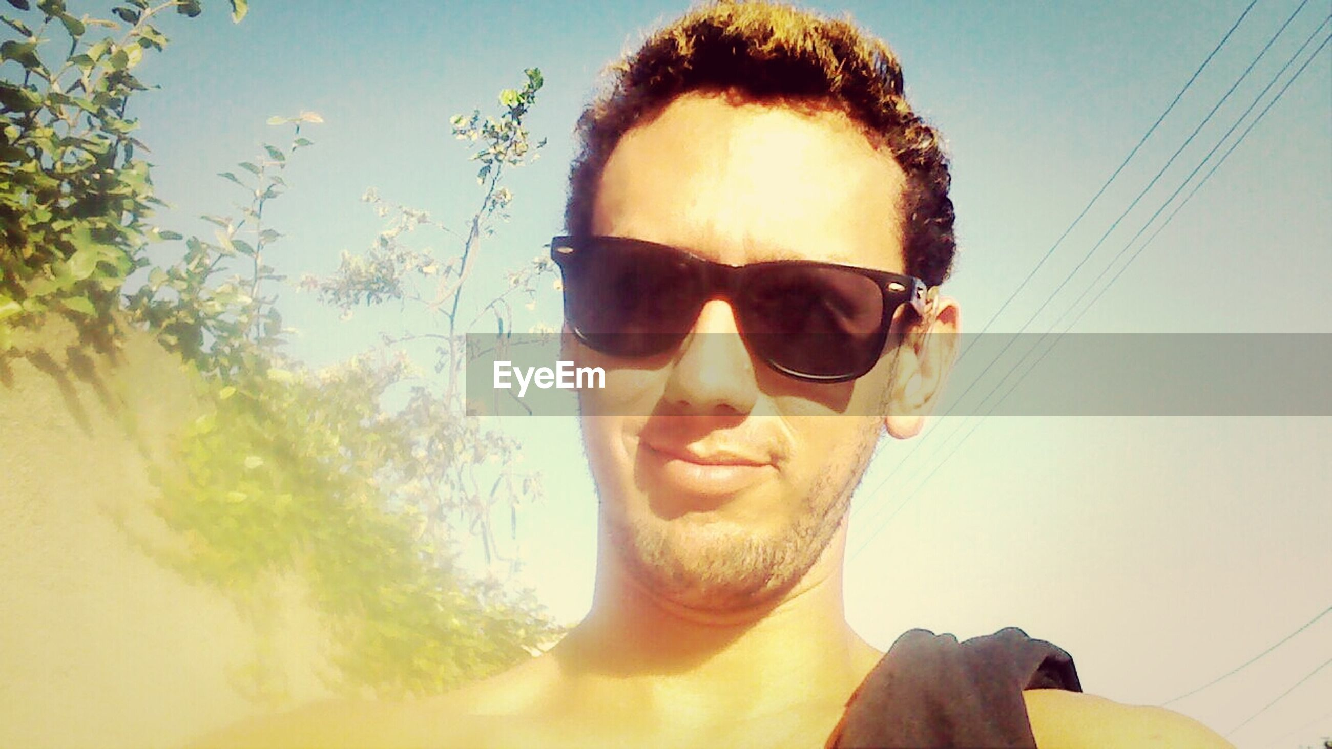 headshot, young adult, portrait, looking at camera, lifestyles, sunglasses, person, front view, leisure activity, young men, close-up, sunlight, mid adult, head and shoulders, mid adult men, sunbeam, sky