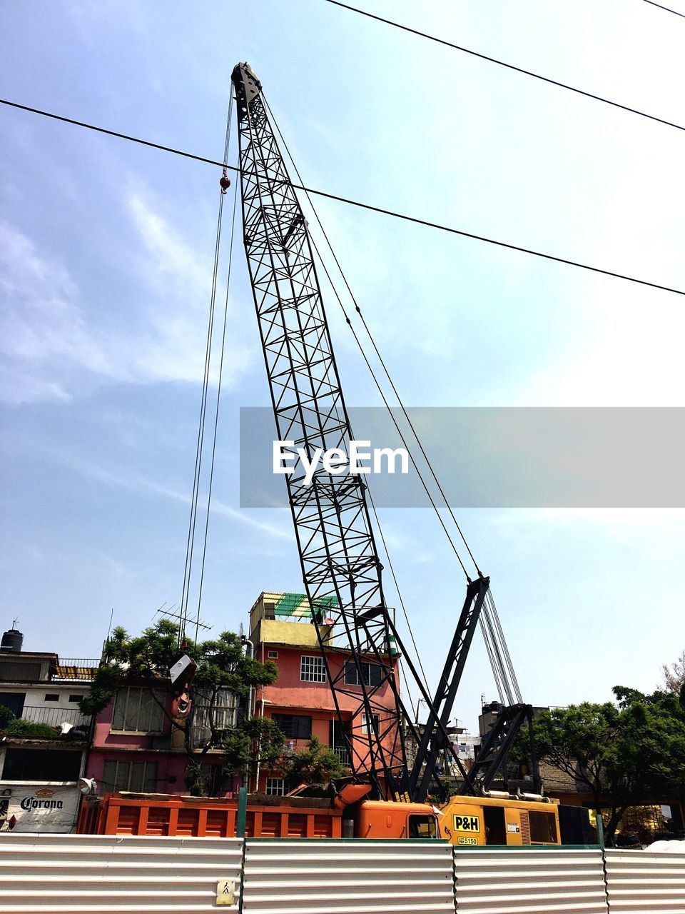 sky, cloud - sky, low angle view, construction site, crane - construction machinery, built structure, construction, day, architecture, cable, outdoors, building exterior, no people, industry, tree, drilling rig, oil pump