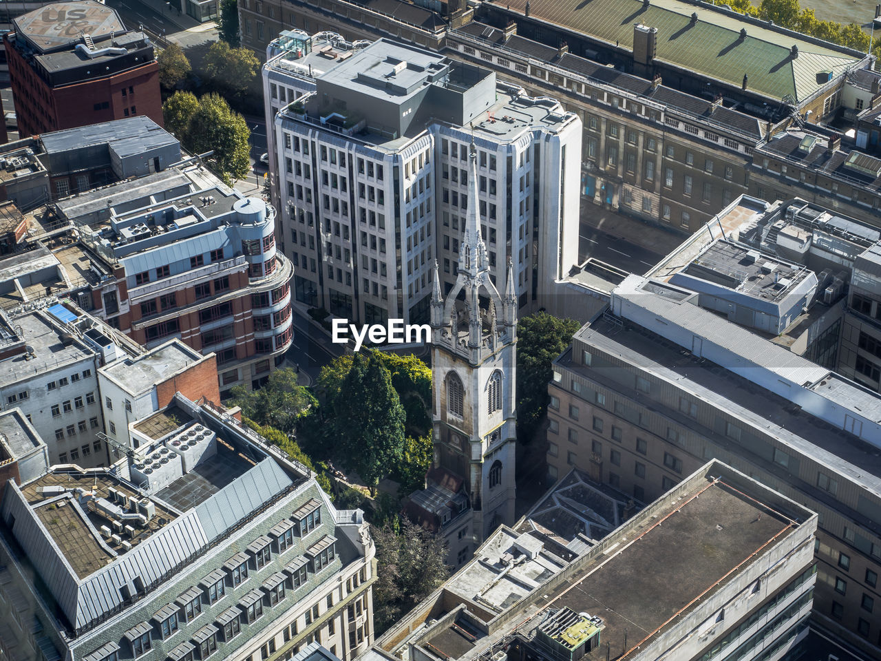 High angle view of old church between modern buildings in london