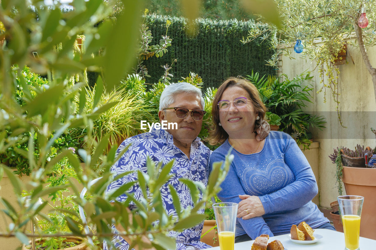 Portrait of smiling senior couple having breakfast while sitting in yard