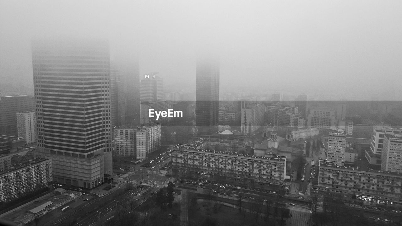 building exterior, city, architecture, built structure, fog, building, cityscape, office building exterior, high angle view, skyscraper, tall - high, nature, sky, no people, day, residential district, landscape, city life, modern, outdoors, smog, financial district, pollution