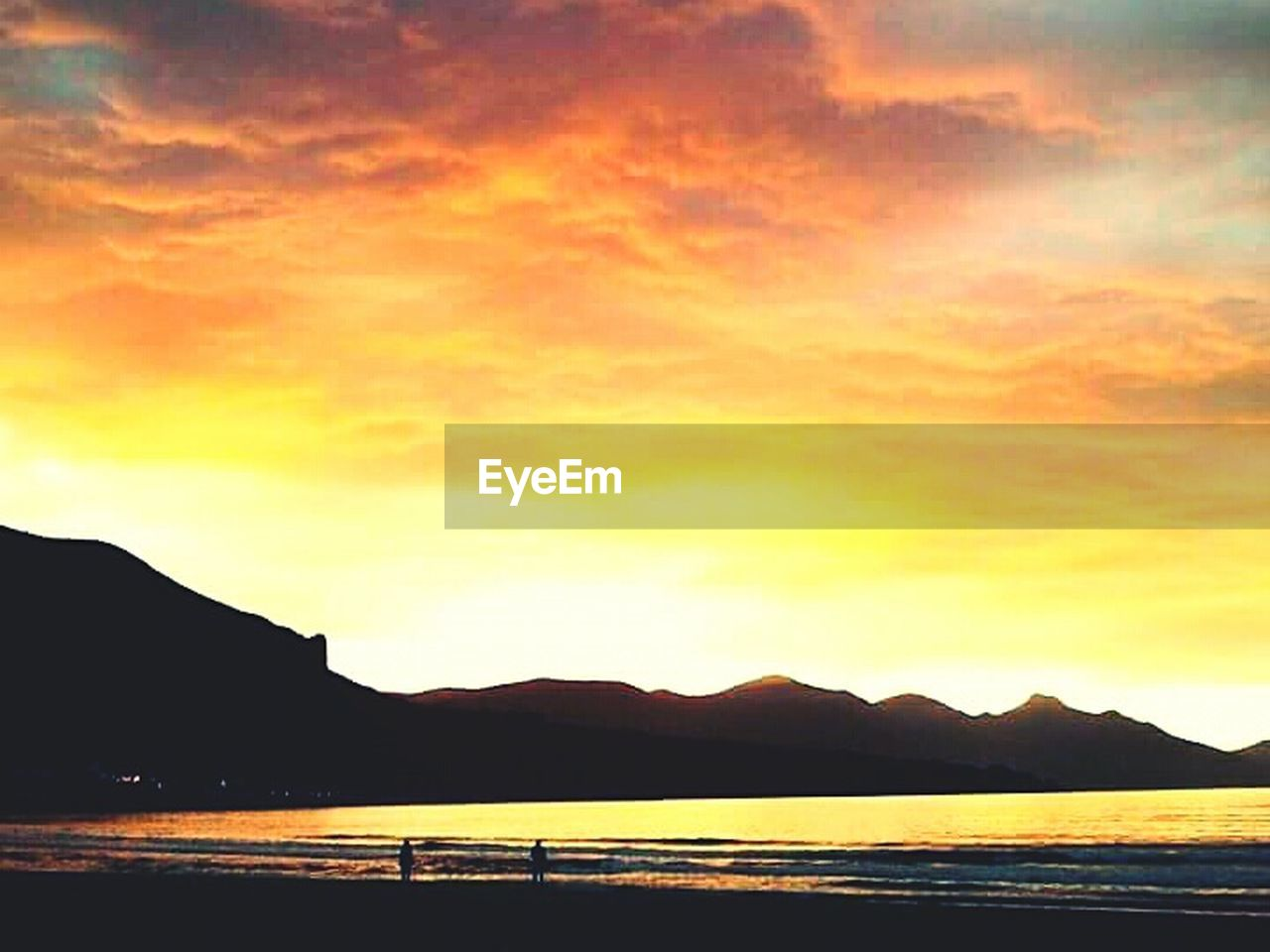 sunset, beauty in nature, scenics, mountain, silhouette, nature, tranquility, water, tranquil scene, dramatic sky, outdoors, sea, no people, travel destinations, mountain range, beach, sky, day