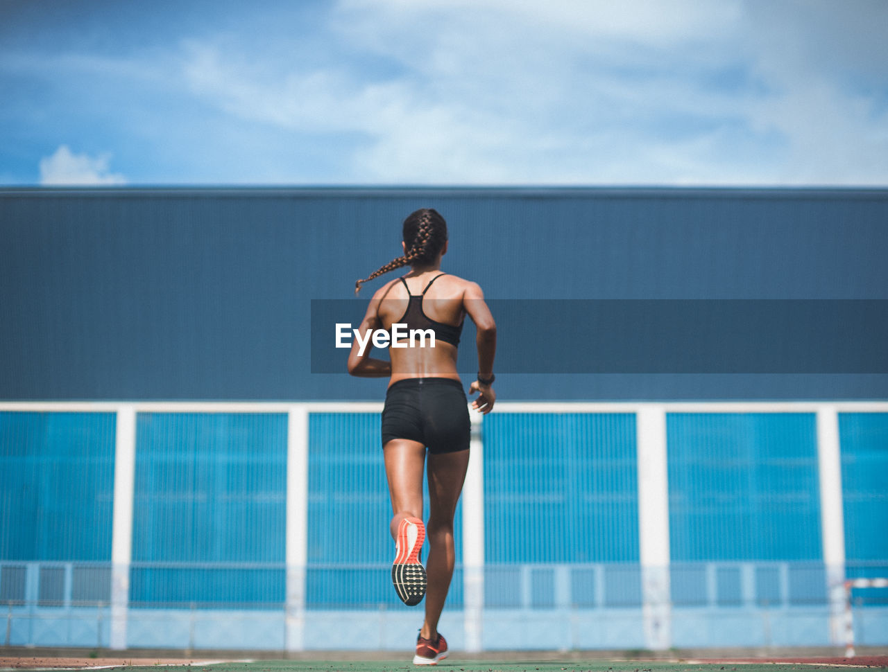 Rear View Of Woman Running On Playing Field