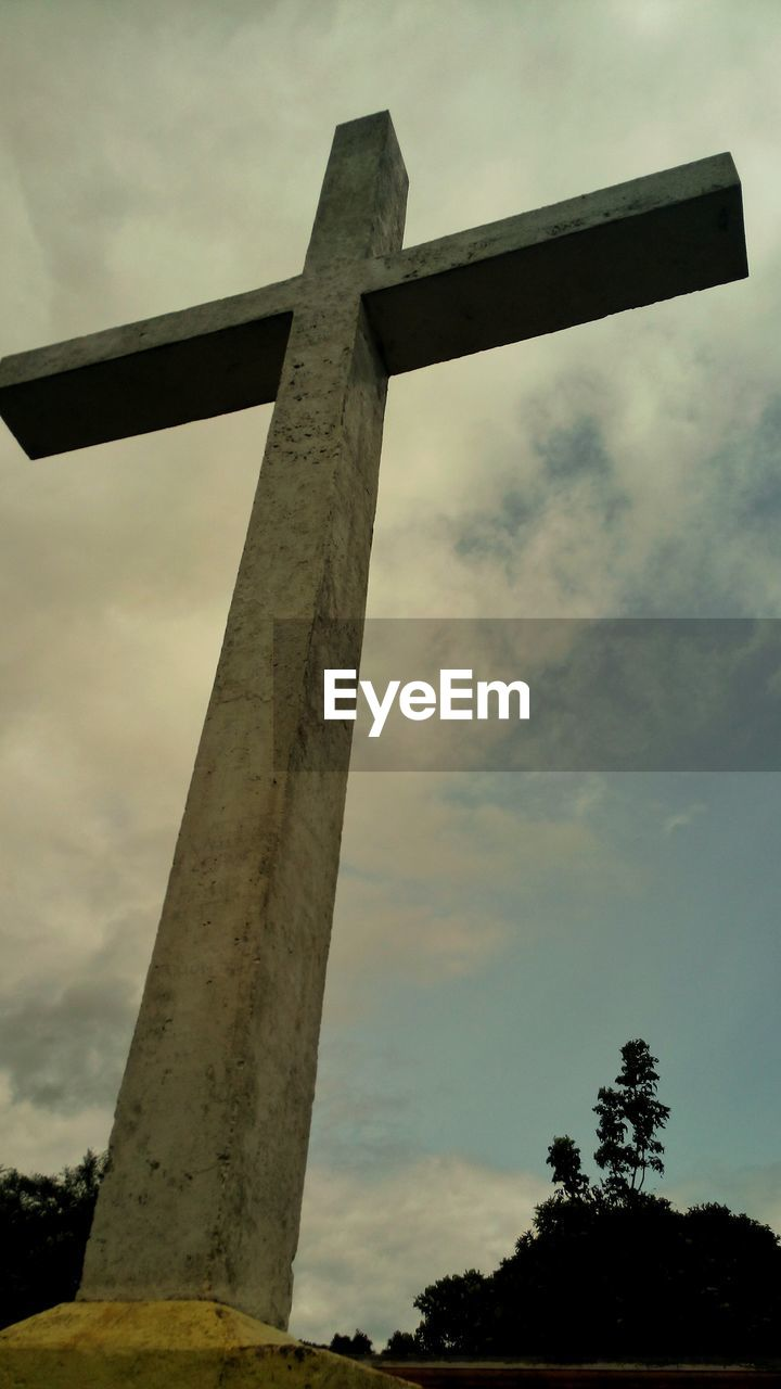 Low angle view of cross against cloudy sky