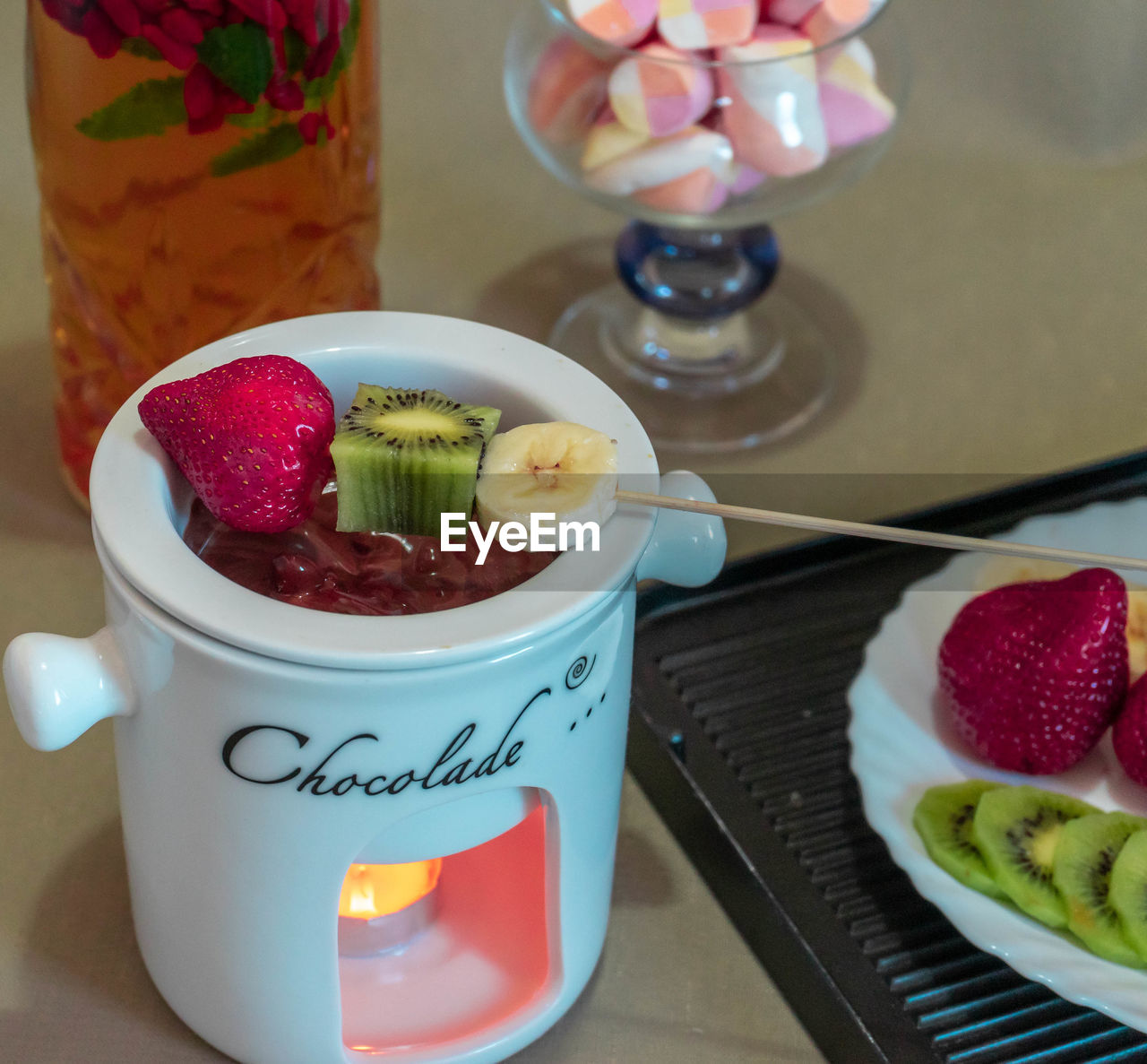 CLOSE-UP OF ICE CREAM WITH FRUITS AND TABLE