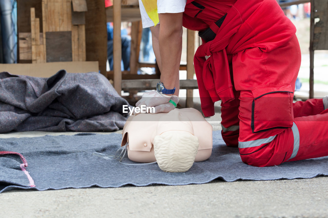 Low section of paramedic performing cpr on dummy
