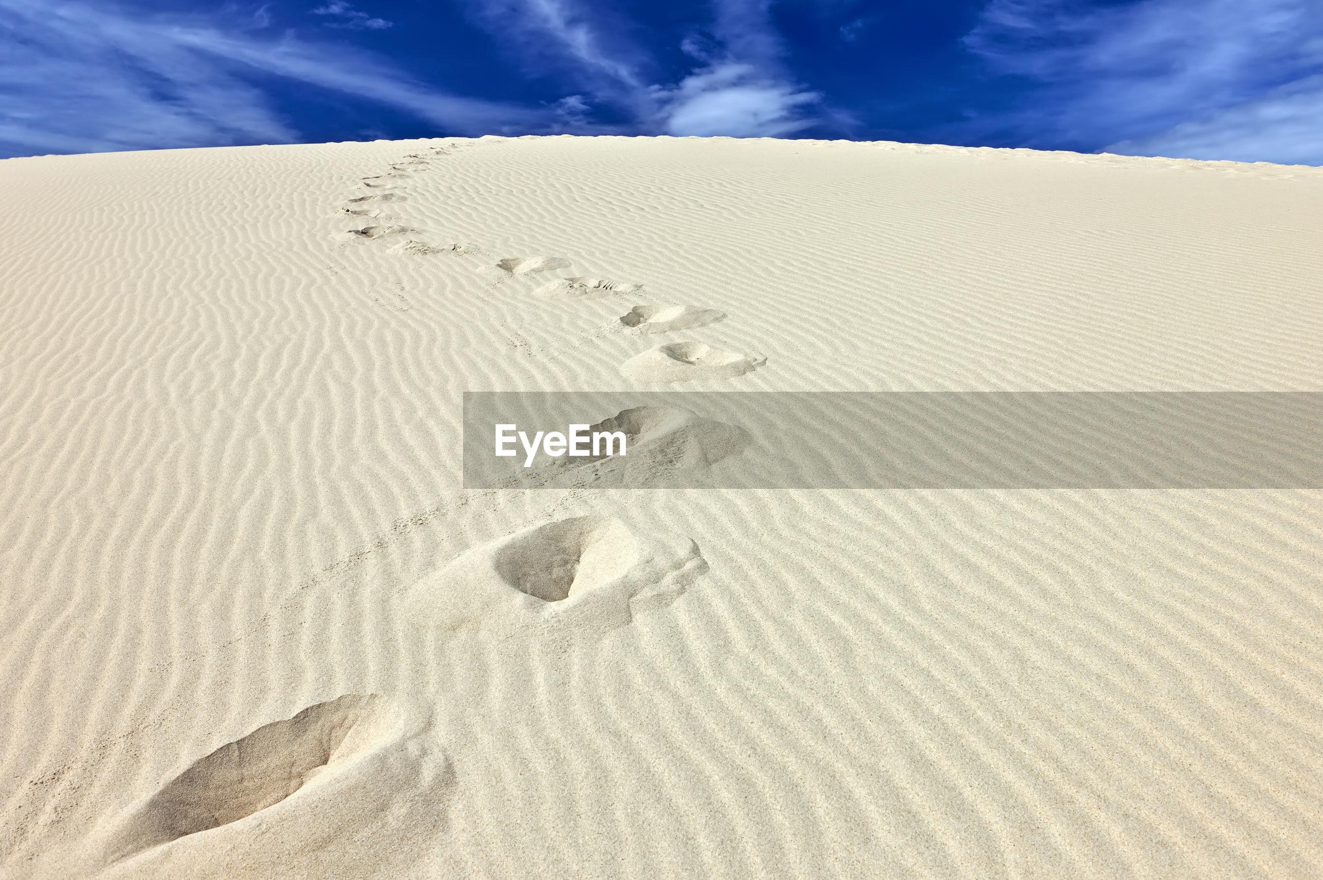 FOOTPRINTS ON SAND DUNE IN DESERT