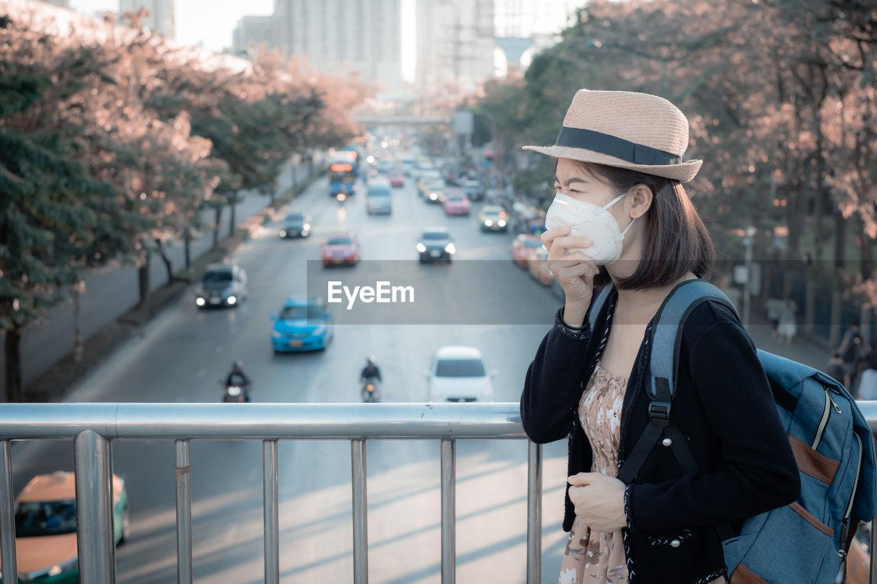 Young woman wearing mask standing on footbridge