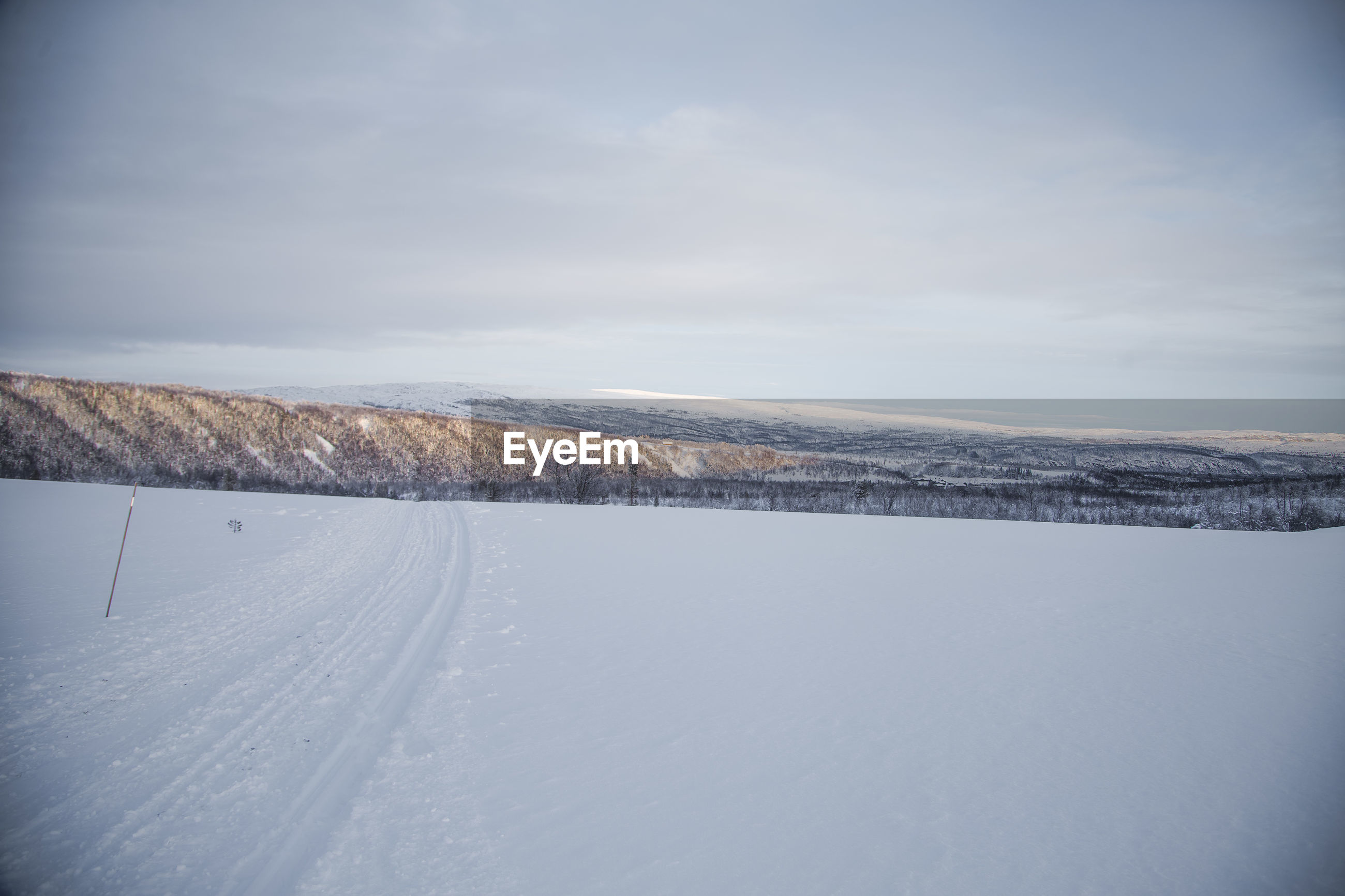 SCENIC VIEW OF SNOW COVERED LANDSCAPE AGAINST SKY DURING WINTER