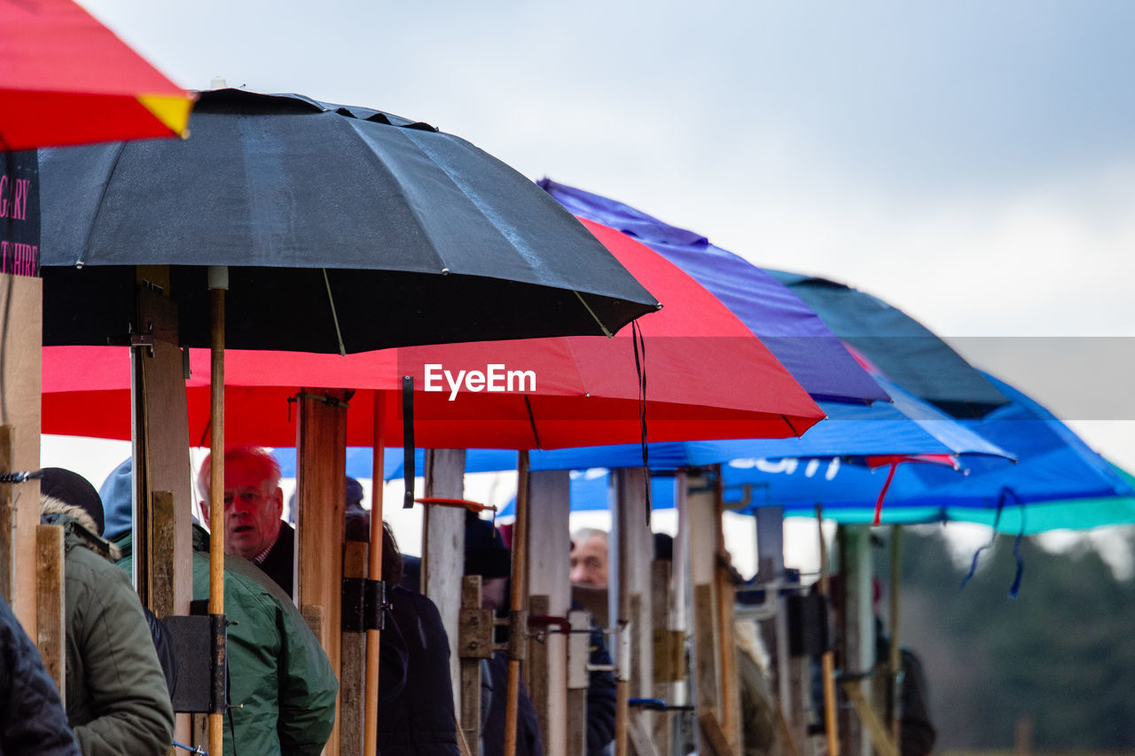 umbrella, protection, sky, day, real people, men, nature, people, group of people, focus on foreground, security, lifestyles, adult, leisure activity, outdoors, flag, incidental people, casual clothing, walking
