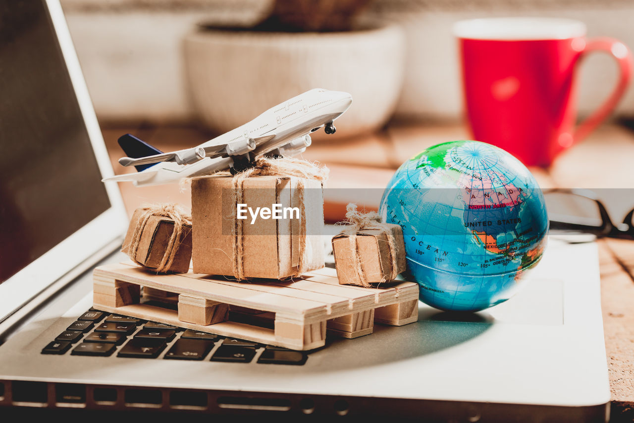 Close-Up Of Model Airplane With Boxes And Globe On Laptop