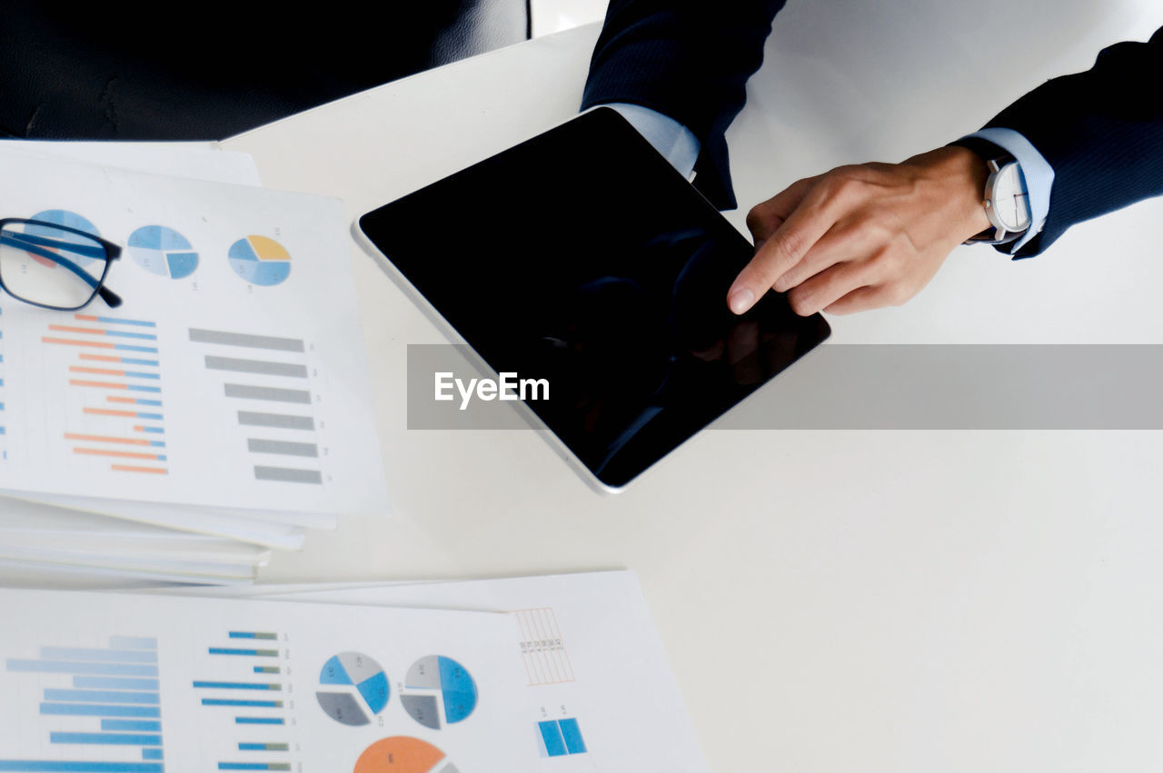 Cropped hands of business person using digital tablet at desk in office