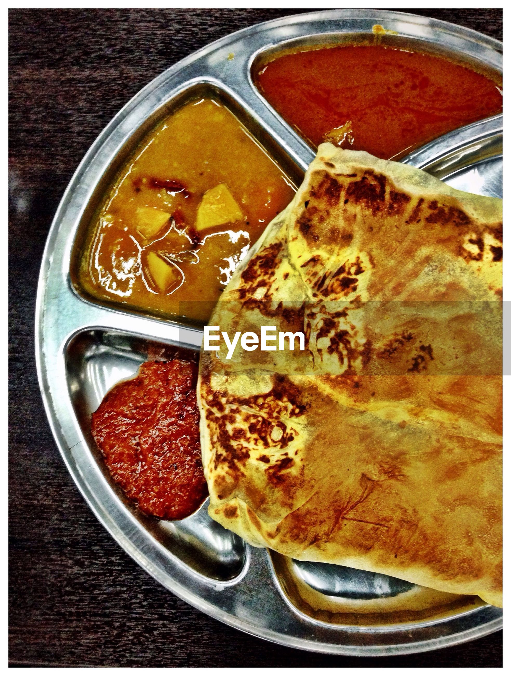 High angle view of roti canai with vegetables in plate
