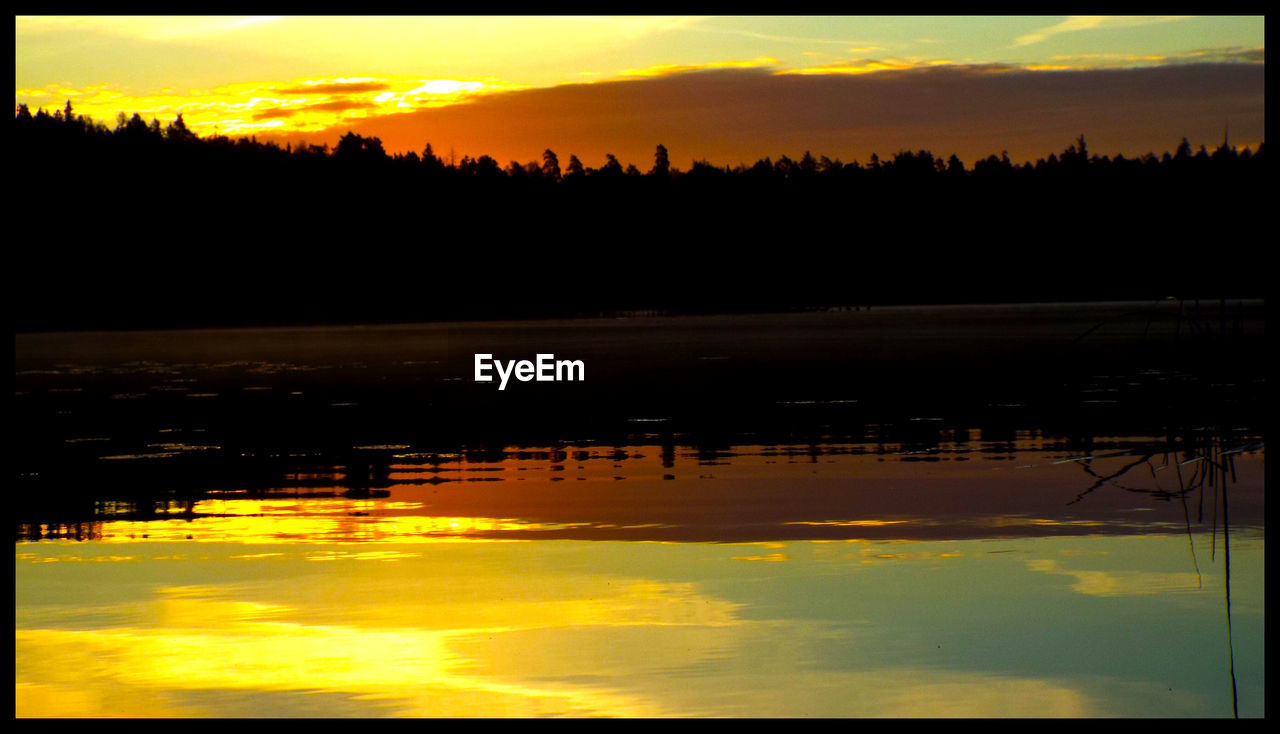 sunset, reflection, scenics, tranquility, nature, sky, tranquil scene, beauty in nature, silhouette, water, outdoors, orange color, no people, lake, cloud - sky, idyllic, landscape, yellow, tree, travel destinations, day