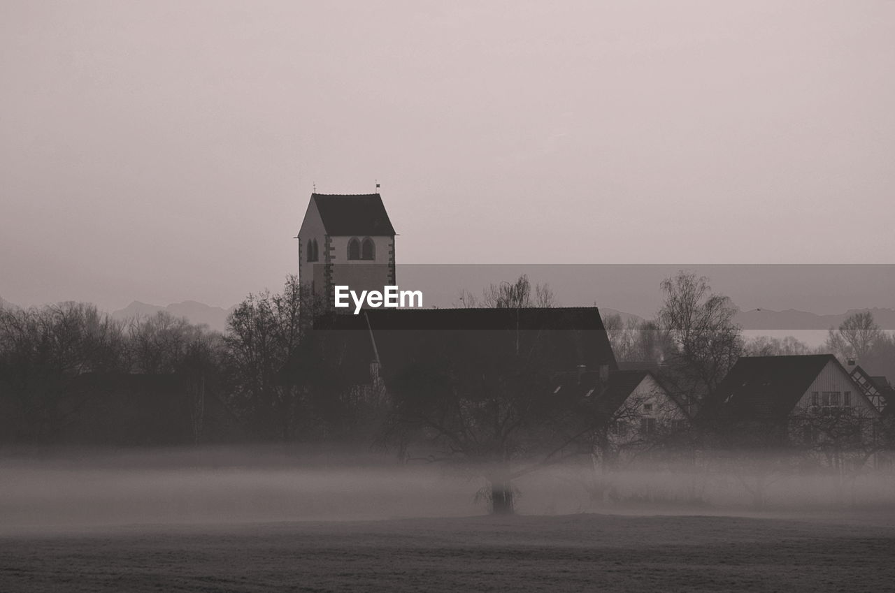 built structure, architecture, building exterior, sky, fog, building, nature, no people, tree, copy space, water, outdoors, agricultural building, day, plant, field, environment