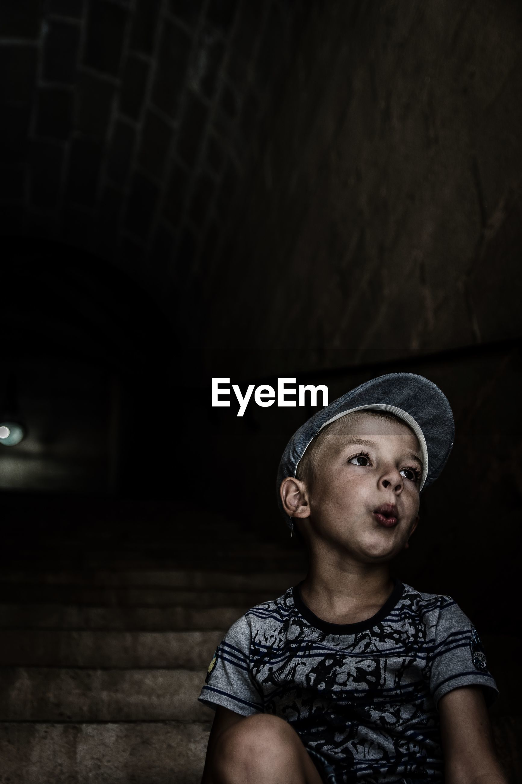 Thoughtful boy wearing cap while sitting on steps in tunnel