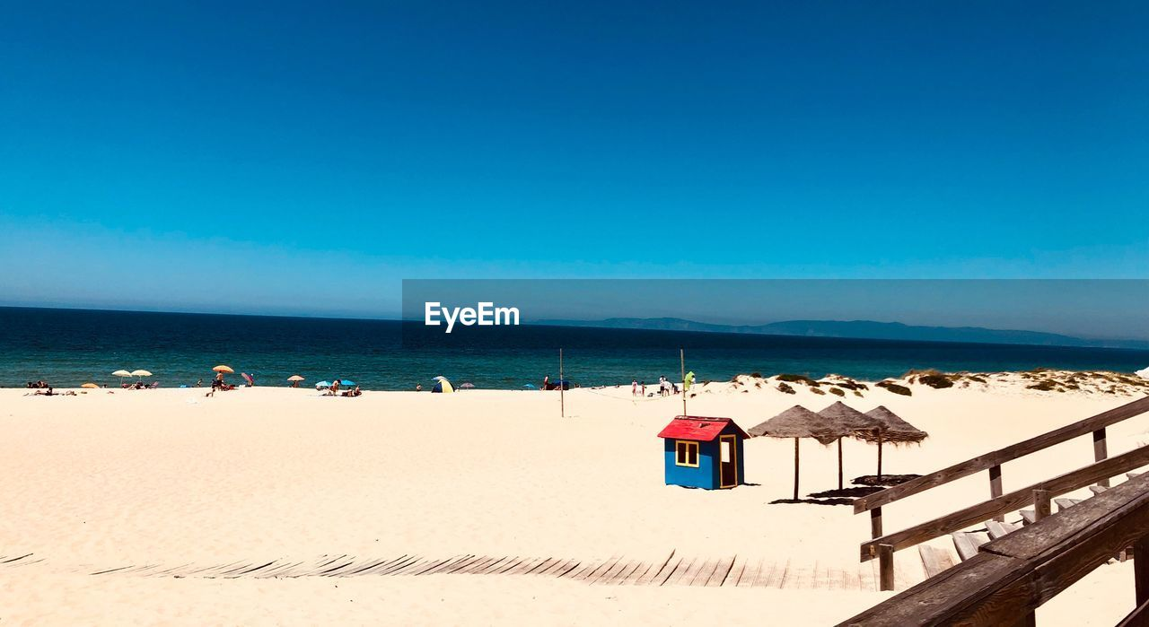 sea, water, sky, beach, land, sand, horizon over water, horizon, blue, scenics - nature, nature, copy space, clear sky, beauty in nature, day, tranquility, sunlight, tranquil scene, incidental people, outdoors