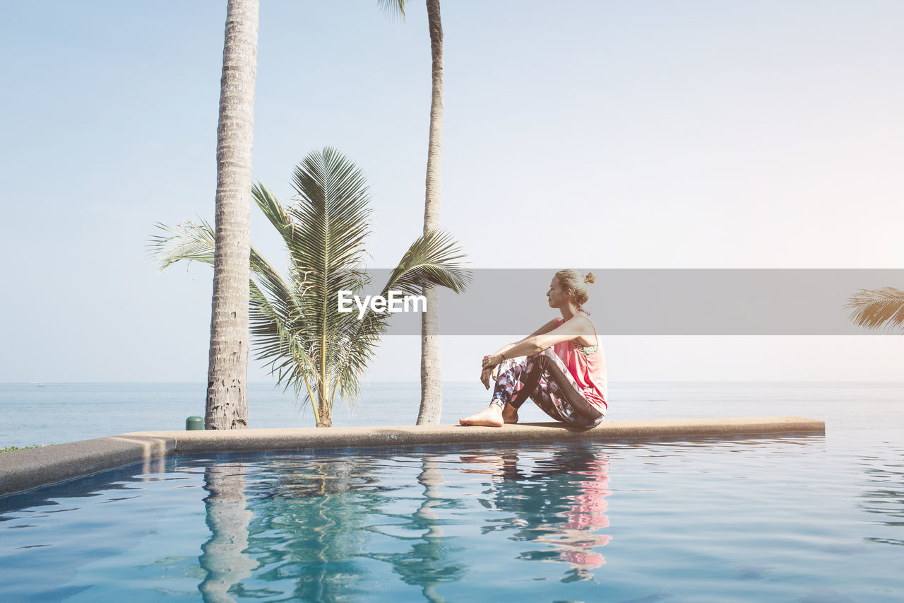 Side View Of Mid Adult Woman Sitting At Infinity Pool Against Sea