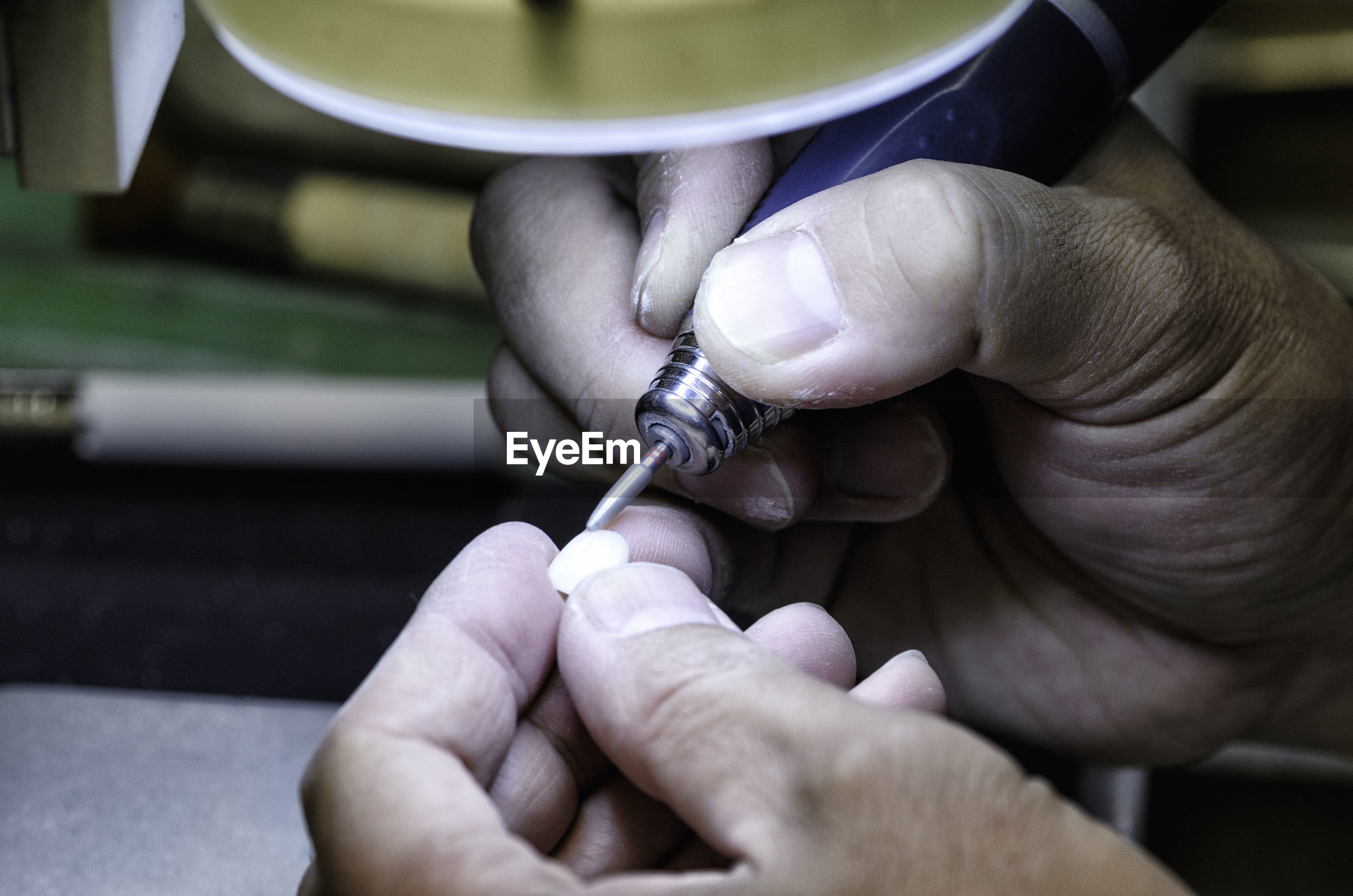 Cropped hands of person cleaning dentures in clinic