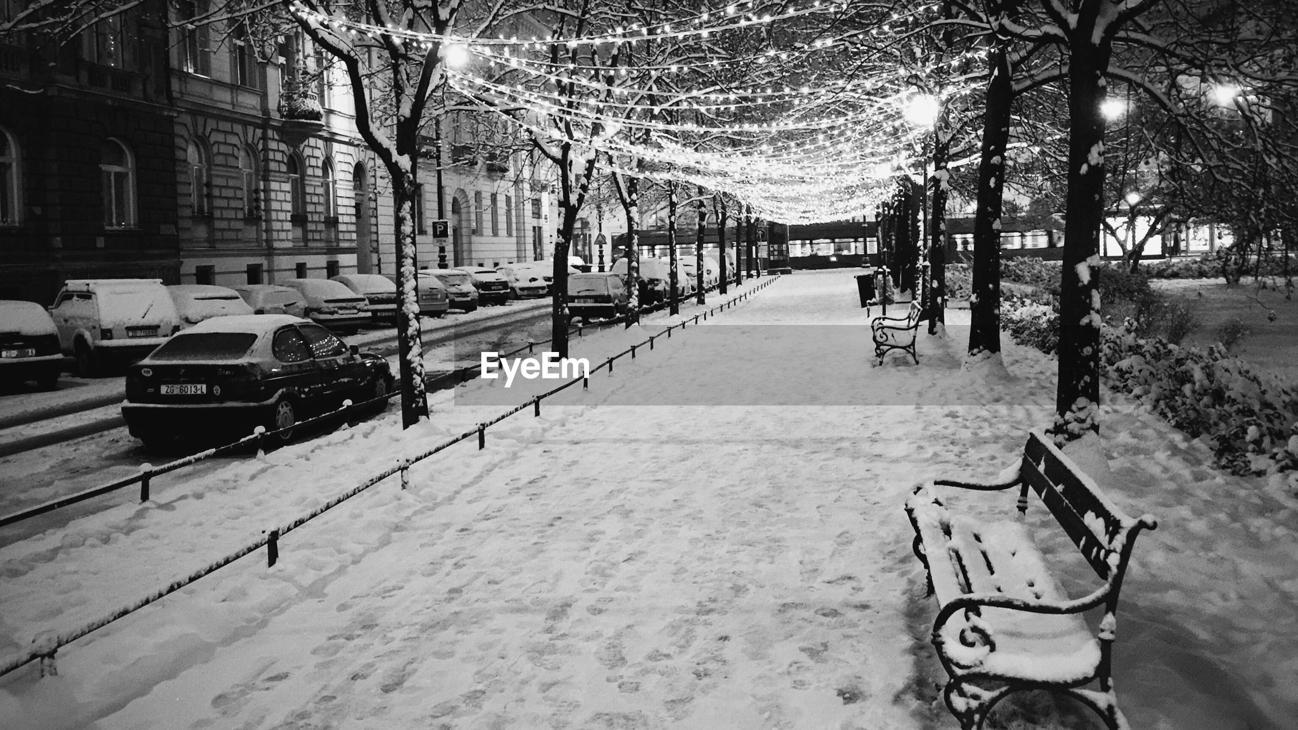 High angle view of empty benches on snow covered illuminated street