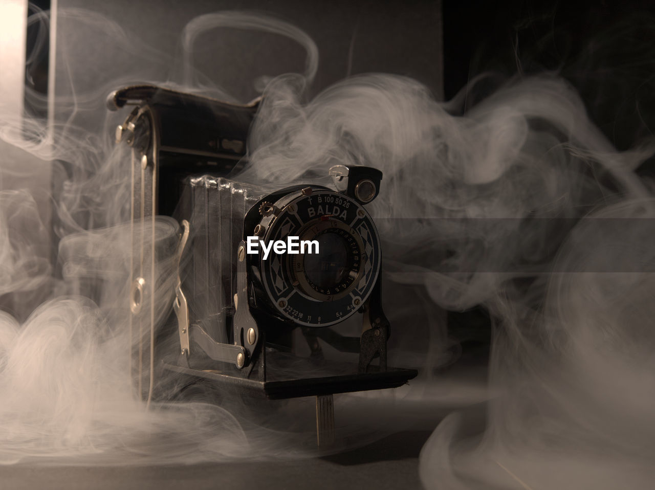 smoke - physical structure, indoors, technology, no people, communication, motion, close-up, antique, retro styled, photography themes, table, still life, the past, digital composite, history, black background, studio shot, equipment, representation