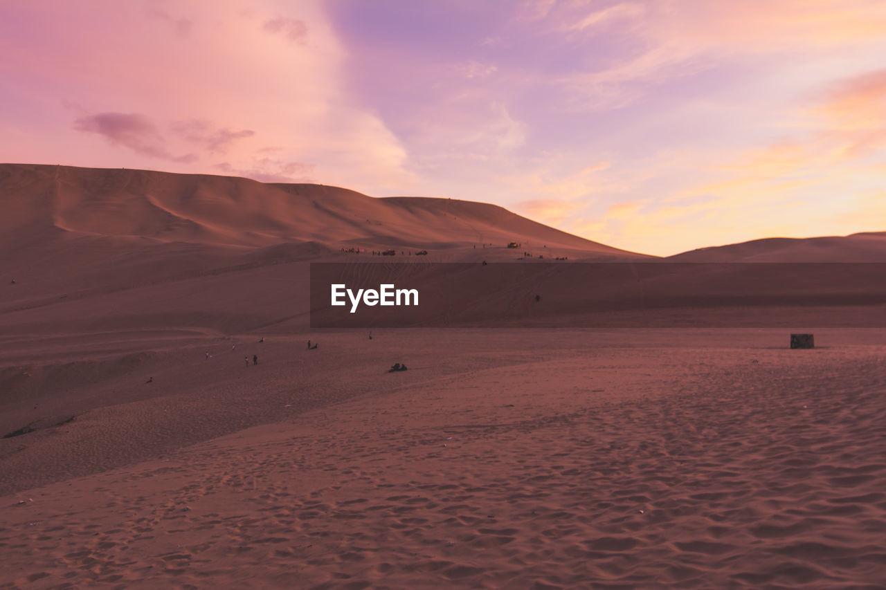 Sand Dunes In Desert Against Cloudy Sky