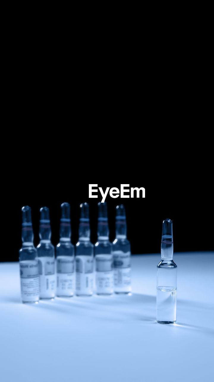 Medicine bottles on table against black background